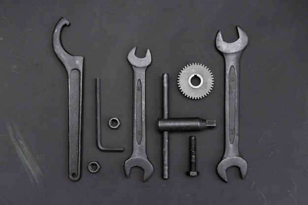 Ferramentas diferentes na mesa escura. ferramentas de chave inglesa, rodas dentadas, chaves de anel, chaves de macaco, roda dentada, parafusos e porcas. Foto Premium