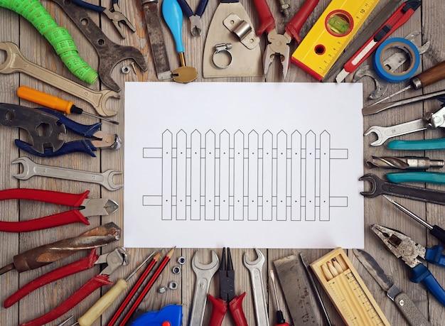 Ferramentas em um assoalho de madeira com um esboço da cerca em uma folha de papel no centro, vista superior. Foto Premium