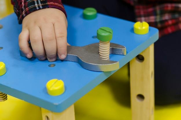 Ferramentas masculinas de brinquedo. chave nas mãos. desenvolvimento de habilidades motoras finas em crianças de acordo com o sistema montessori. brinquedos de madeira para crianças. Foto Premium