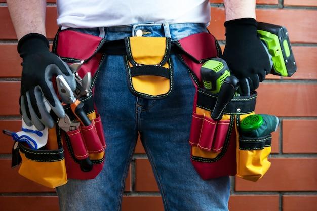 Ferramentas no cinto para ferramentas. o construtor está segurando uma chave de fenda elétrica Foto Premium
