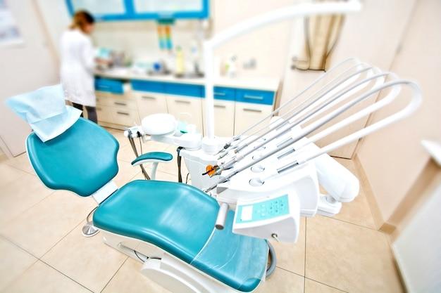 Ferramentas profissionais de dentista e cadeira no consultório odontológico. Foto gratuita