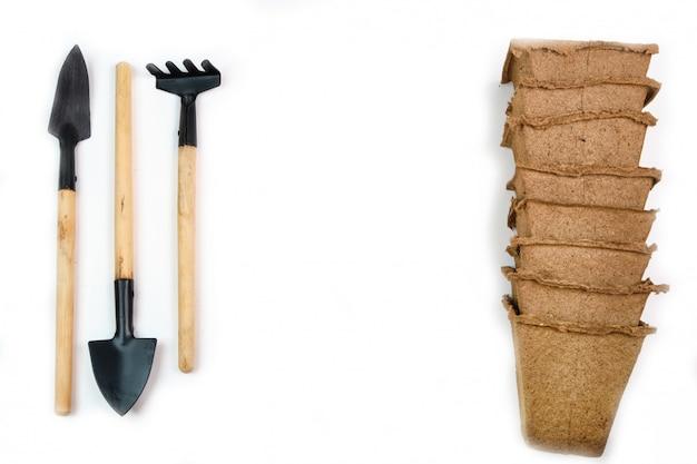 Ferramentas, sementes, vasos de turfa e terra prensada para mudas. copyspace para texto, vista superior. cultivo de alimentos no peitoril da janela. flatlay em branco espaço de madeira Foto Premium