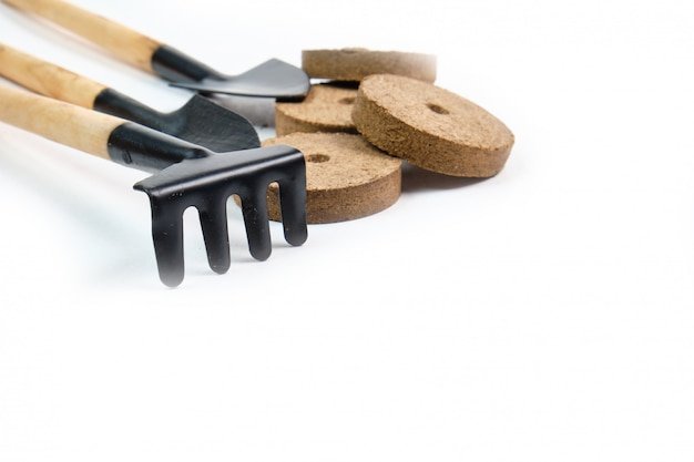 Ferramentas, sementes, vasos de turfa e terra prensada para mudas Foto Premium