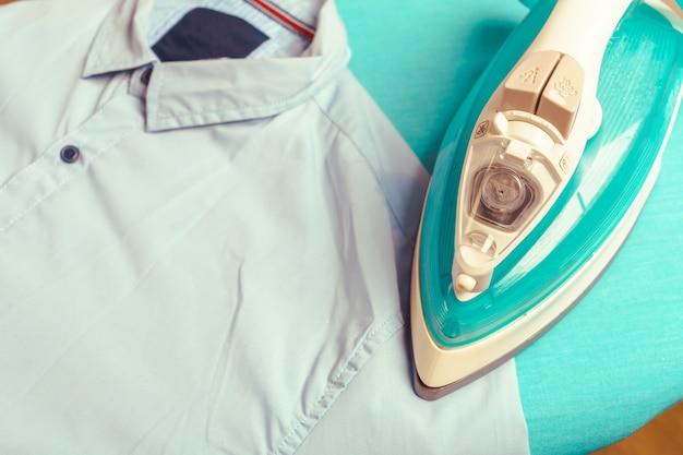 Ferro na tábua de passar roupa na luz de fundo interior de casa Foto Premium