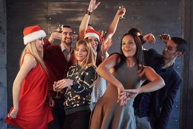 Festa com os amigos. eles amam o natal. grupo de jovens alegres carregando estrelinhas e taças de champagne dançando na festa de ano novo e olhando feliz. conceitos sobre estilo de vida de união Foto Premium