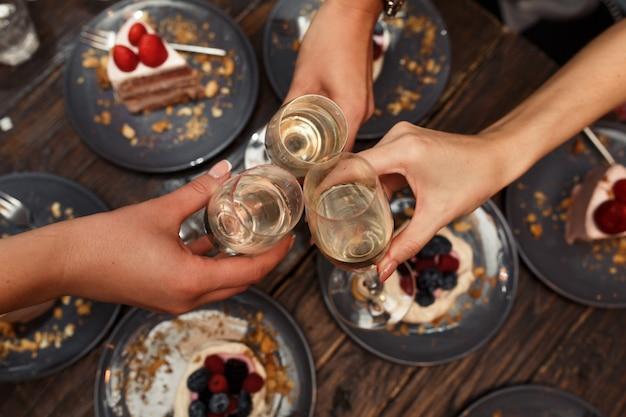 Festa das meninas. as meninas elogiam vidros com champanhe no restaurante. Foto Premium