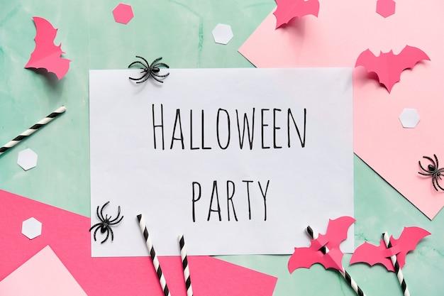 Festa de halloween de texto em fundo de papel em camadas em verde-menta e rosa pastel. postura plana, decoração de festa de halloween. Foto Premium