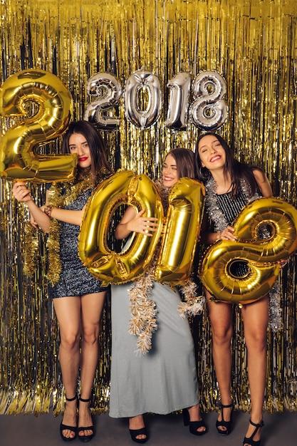 Festa do ano novo com três garotas felizes Foto gratuita