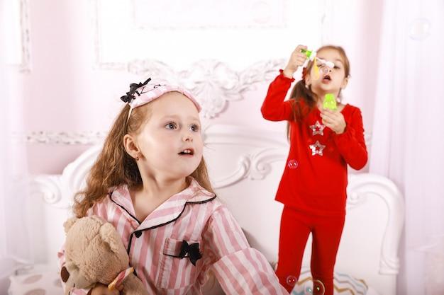 Festa do pijama para crianças, meninas-crianças vestidas de pijama brilhante, jogo de bolhas Foto gratuita
