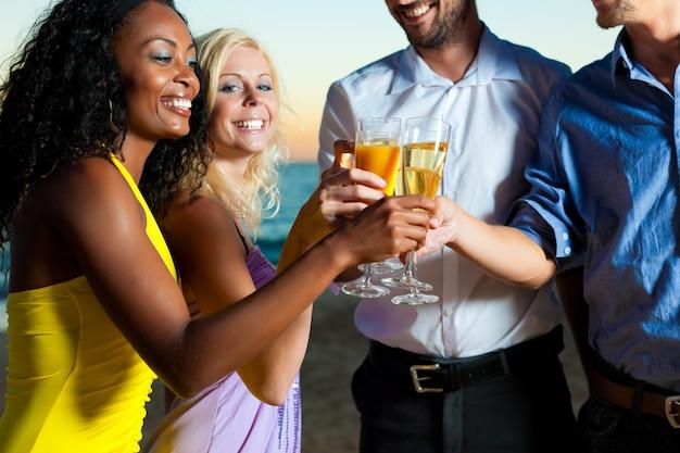 Festa na praia com amigos brindando com champanhe Foto Premium