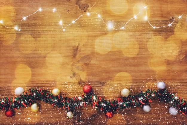 Festão da luz de natal no fundo de madeira. Foto gratuita