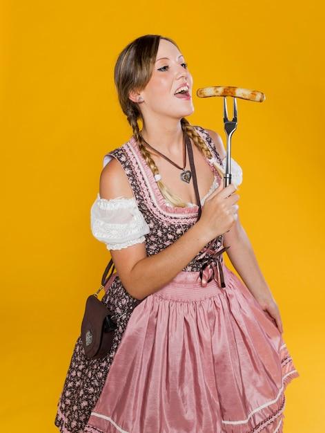 Festiva mulher comendo salsicha tradicional Foto gratuita