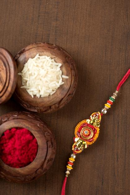 Festival indiano: raksha bandhan com um elegante rakhi, grãos de arroz e kumkum. pulseira tradicional indiana, símbolo de amor entre irmãos e irmãs. Foto Premium