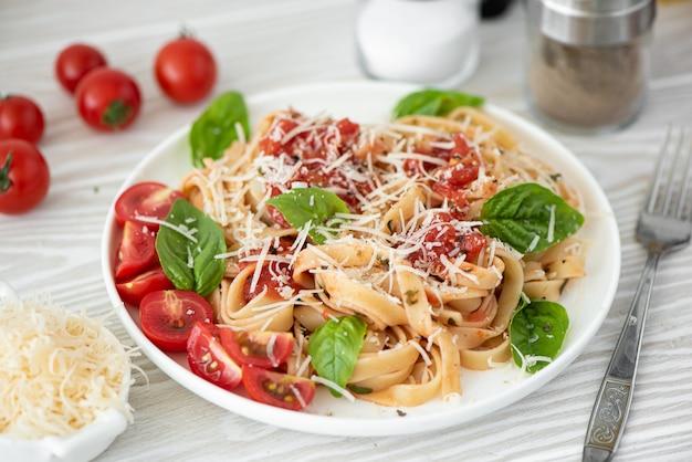 Fettuccine com molho de tomate, parmesão e manjericão na chapa branca Foto Premium