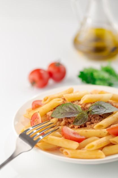 Fettuccine de macarrão à bolonhesa com molho de tomate e manjericão no prato branco sobre branco Foto Premium