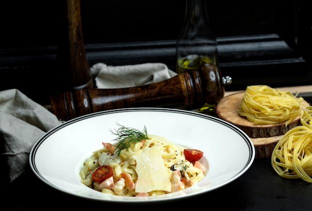 Fettuccini de frutos do mar com molho cremoso, parmesão coberto com tomate cereja e endro Foto gratuita