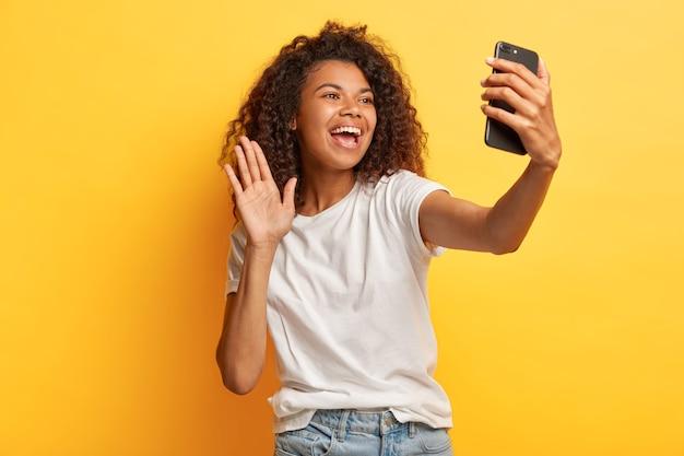 Fico feliz, mulher feliz, de pele escura, com penteado afro, segura o celular moderno na frente do rosto, acena com a palma da mão na câmera, faz videochamada, vestida com roupa casual Foto gratuita