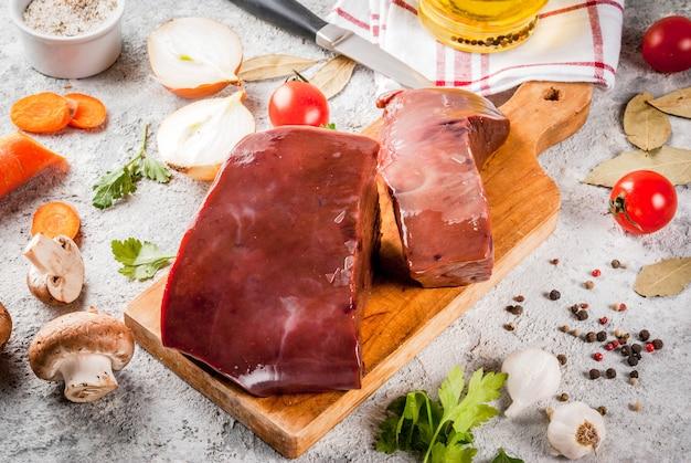 Fígado de bovino cru com especiarias, ervas e legumes, mesa de pedra cinza Foto Premium