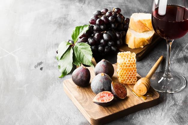 Figo, uvas, pão, mel e vinho tinto Foto Premium