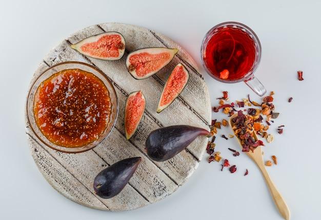 Figos com geléia, xícara de chá, ervas secas planas leigos na placa branca e de madeira Foto gratuita