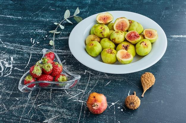 Figos em um prato branco com morangos em um copo de vidro. Foto gratuita