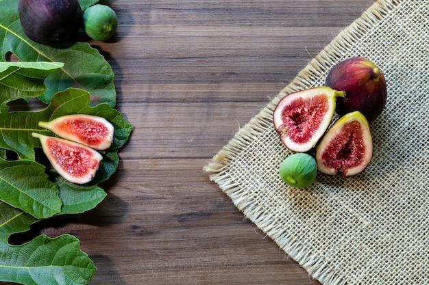 Figos, folhas verdes na superfície de madeira rústica Foto Premium