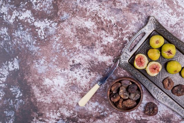 Figos inteiros secos e fatiados em bandeja metálica e xícara de madeira. Foto gratuita