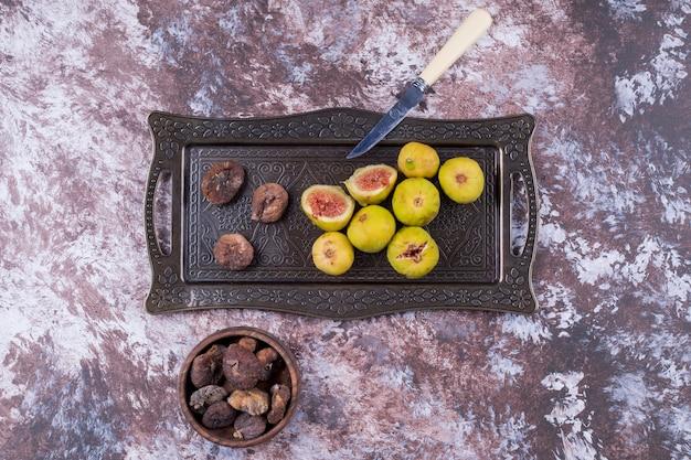 Figos inteiros secos e fatiados em tabuleiro metálico e em chávena de madeira ao centro. Foto gratuita