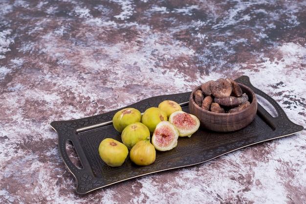 Figos inteiros secos e fatiados em tabuleiro metálico e em chávena de madeira, vista de ângulo. Foto gratuita