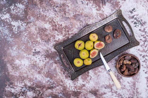 Figos inteiros, secos e fatiados em uma bandeja metálica e em um copo de madeira com uma faca à parte. Foto gratuita