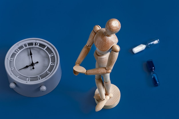 Figura de madeira de um homem azul com um relógio Foto gratuita