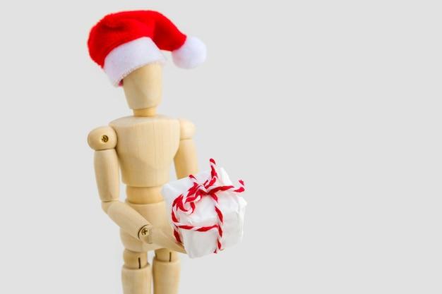 Figura de madeira - manequim de arte com chapéu de papai noel vermelho com caixa de presente. negócios e conceito de design para o natal Foto Premium