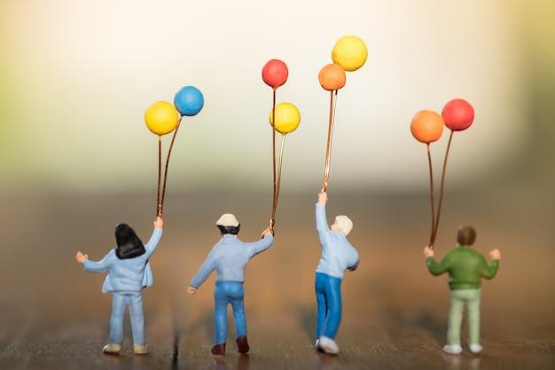 Figura diminuta das crianças com os balões coloridos que estão, andando e jogando junto na tabela de madeira. Foto Premium