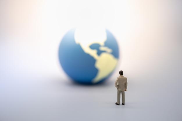 Figura diminuta do homem de negócios que está e que olha à mini esfera do mundo. Foto Premium