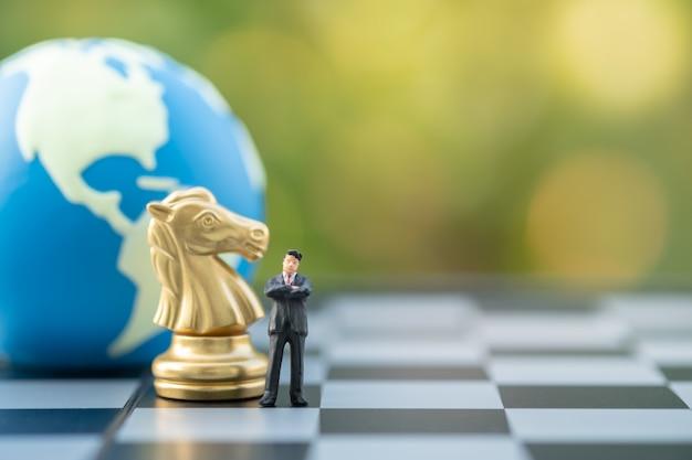Figura diminuta do homem de negócios que está no tabuleiro de xadrez com xadrez do cavaleiro do ouro e esfera do mundo. Foto Premium