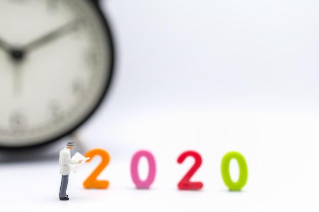 Figura em miniatura de empresário em pé e lendo um jornal com número de plástico colorido 2020 e relógio Foto Premium