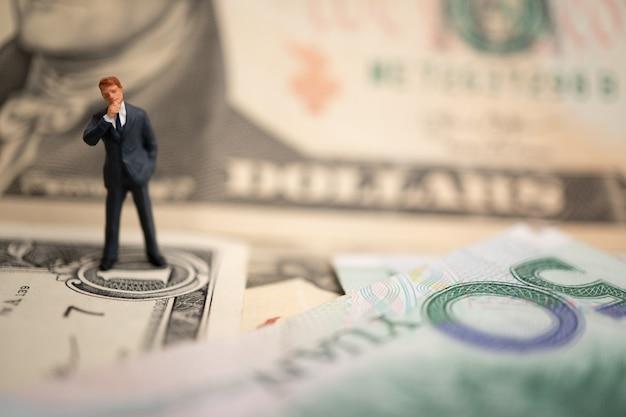 Figura empresário de pé na nota de dólar e yuan, estão de mãos dadas para o sucesso em acordos comerciais. Foto Premium