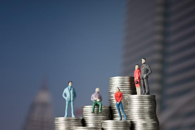 Figura empresário em miniatura em pé na pilha de moedas Foto Premium
