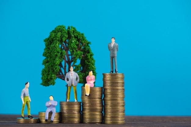 Figura empresário em miniatura na pilha de moedas com pequena árvore Foto Premium