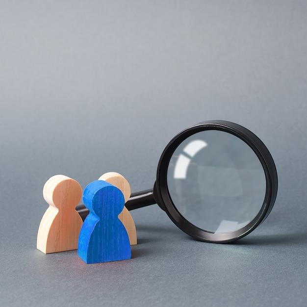 Figura humana de madeira três fica perto de uma lupa em um cinza Foto Premium