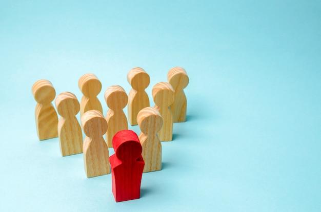 Figuras de madeira de pessoas. o chefe da equipe de negócios indica a direção Foto Premium