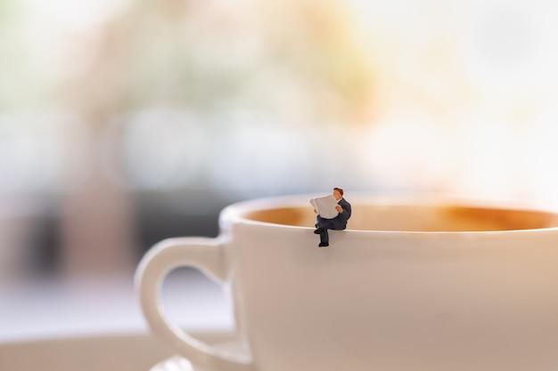 Figuras de miniatura de empresário mini pessoas sentado e ler um jornal sobre a xícara de café quente. Foto Premium