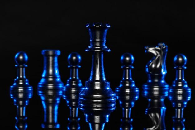 Figuras de xadrez em fundo preto com luz de fundo azul Foto Premium