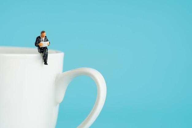 Figuras em miniatura de negócios sentado e ler um livro, ler jornal, esperando, conversando e relaxar na xícara branca de café quente. Foto Premium