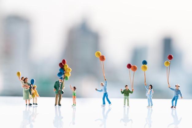 Figuras pequenas das crianças que prendem o balão com fundos da cidade. Foto Premium
