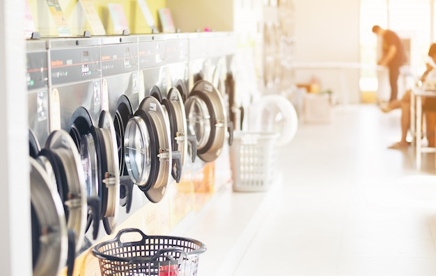 Fila de máquinas de lavar roupa industrial na lavanderia em uma lavanderia pública, com lavanderia em uma cesta, tailândia Foto Premium