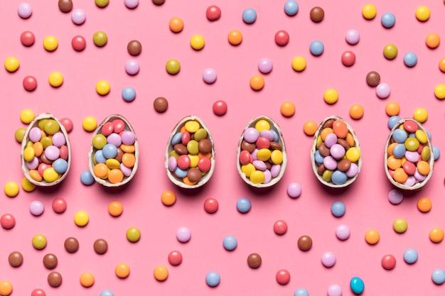Fila de ovos de páscoa quebrados com doces gema no pano de fundo rosa Foto gratuita