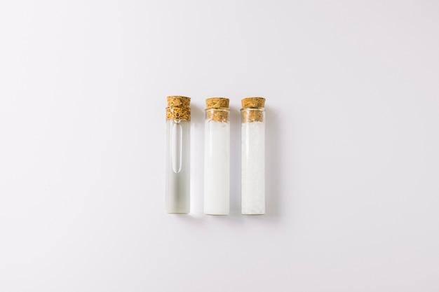 Fila de três óleos essenciais em tubos de ensaio em pano de fundo branco Foto gratuita