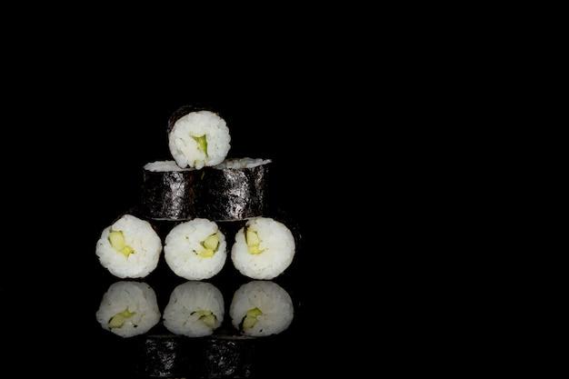 Filadélfia roll com salmão, queijo e pepino em um fundo preto com reflexão Foto Premium