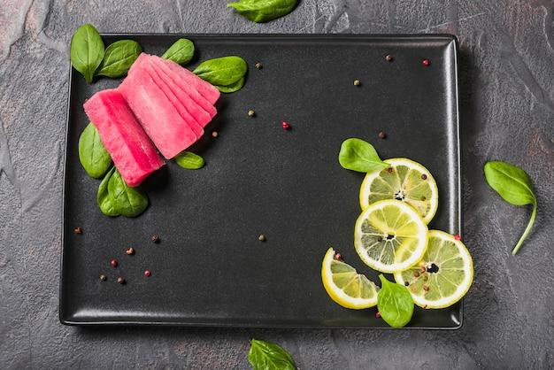 Filé de atum cru com folhas de manjericão e limão Foto gratuita
